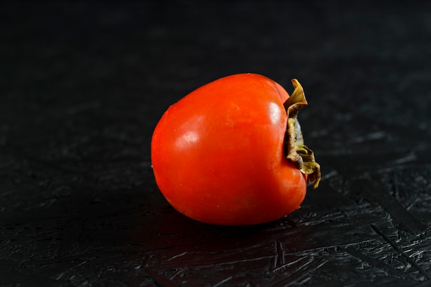 Autumn fruits. persimmon on a black wooden surface