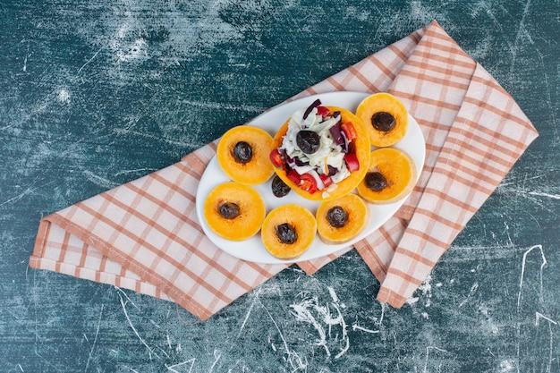 Piatto di frutta autunnale isolato sulla superficie blu.