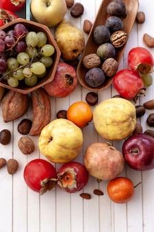 Autumn fruits on white wooden table
