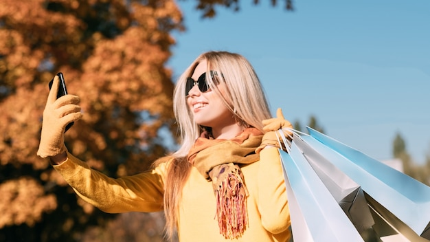 Autumn fun stylish lady with shopping bags taking selfie on smartphone