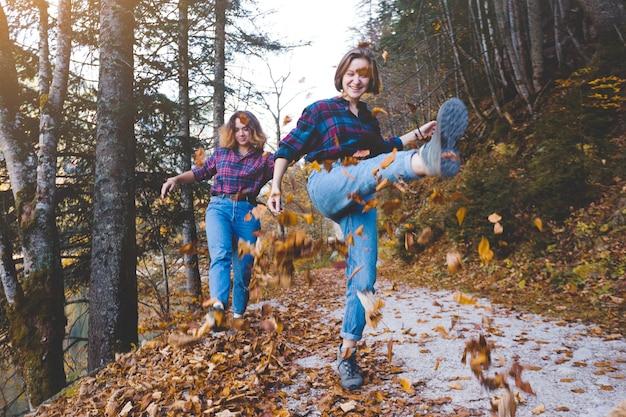 가을의 즐거움. 숲에서 두 명의 행복한 소녀가 마른 잎을 던졌습니다