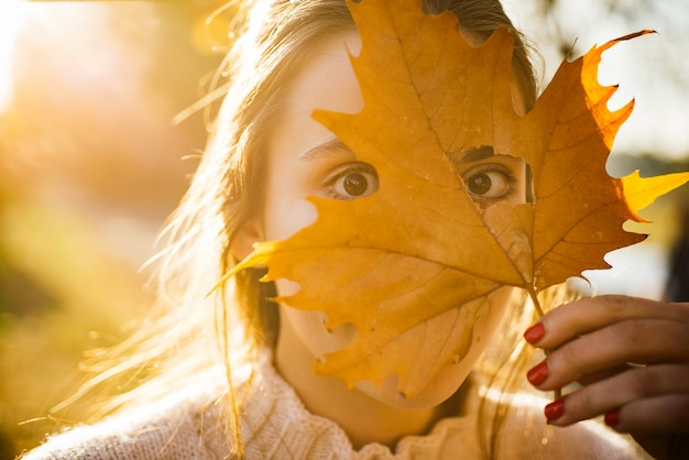 Autumn. funny face. woman holding yellow maple leaves and hiding eyes.