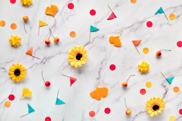 Autumn gingko leaves, paper confetti and toothpick flags. flat lay on white marble table. abstract fall seasonal background