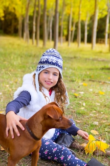 Autumn girl in poplar tree forest playing with dog