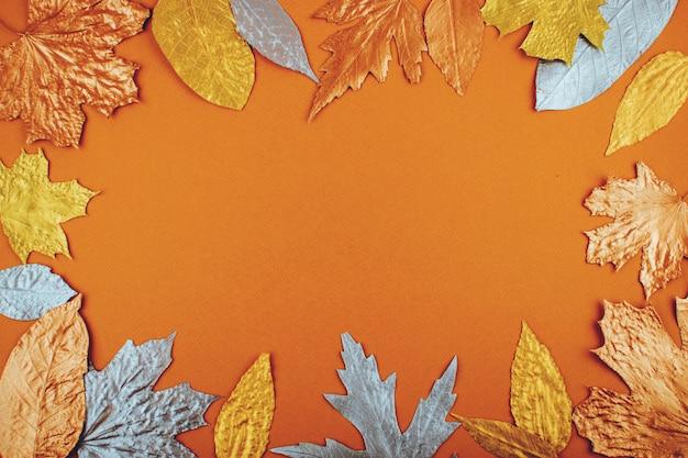 Autumn golden leaves frame on orange paper background