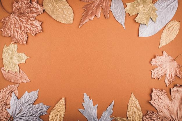 Autumn golden leaves frame on orange
