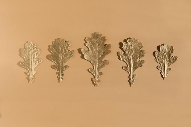 ベージュ、フラットレイに秋の黄金の大理石の葉