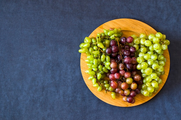 Autumn grapes on the blue table, harvesting seasonal fruit