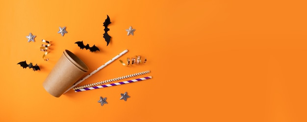 Autumn halloween composition of paper glasses, multicolored tubules for drinks, black paper bats