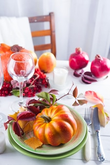 Autumn halloween or thanksgiving day table setting. fallen leaves, pumpkins, spices