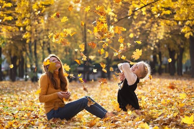 秋。幸せな家族-屋外で娘と笑顔の母は黄色のカエデの葉を投げます