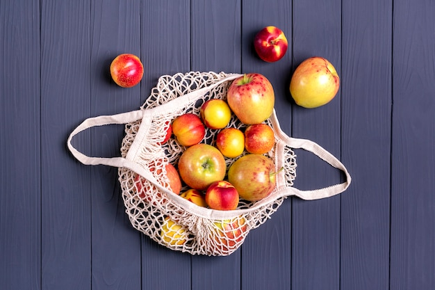 Autumn harvest. eco friendly mesh shop bag with juicy apple, nectarine on dark gray wooden surface.