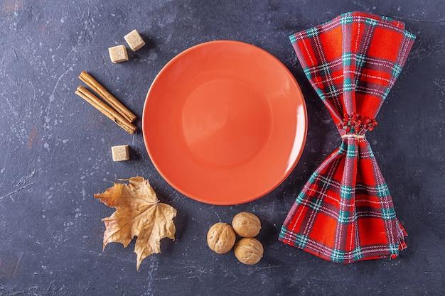 Праздник осеннего урожая и сервировка стола в день благодарения. пустая тарелка и клетчатая салфетка