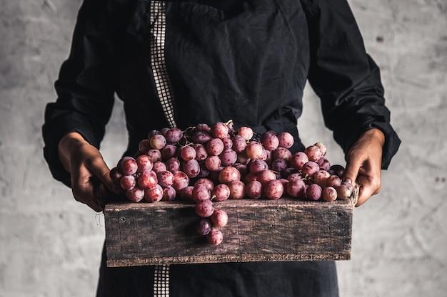 秋の収穫。木箱に新鮮なブドウの房。女性の手で熟したブドウ。