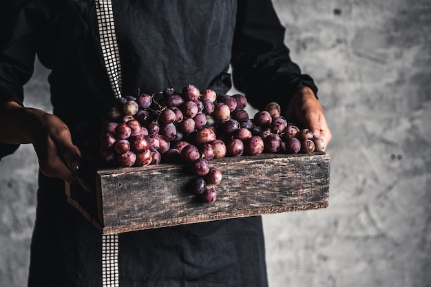 Autumn harvest. fresh grapes bunch in wooden box. ripe grape in woman hands.