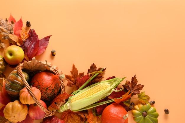 バスケット、カボチャ、リンゴ、トウモロコシの穂軸、テキスト用のスペースとオレンジ色の背景にカラフルな葉の秋の収穫。感謝祭のモックアップ。上からの眺め。