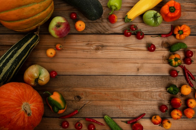 木の板に野菜や果物の秋の収穫。カボチャ、メロン、ズッキーニ、トマト、リンゴ、コショウ。自然からのビタミン。上面図。テキスト用のスペース。