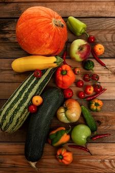 木の板に野菜や果物の秋の収穫。カボチャ、メロン、ズッキーニ、トマト、リンゴ、コショウ。自然からのビタミン。上面図。垂直。