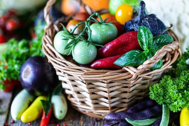 Осенний урожай овощей в плетеной корзине: помидоры, фасоль, тыква, тыква, капуста, зелень, петрушка.