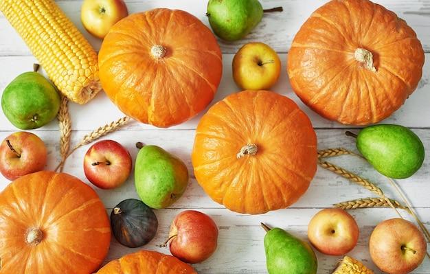秋の収穫カボチャ。秋の収穫野菜と果物。カボチャ、リンゴ、梨、トウモロコシのテーブル。感謝祭のテーブル。ハロウィーンまたは季節の秋。グリーティングカード。秋のキッチン。