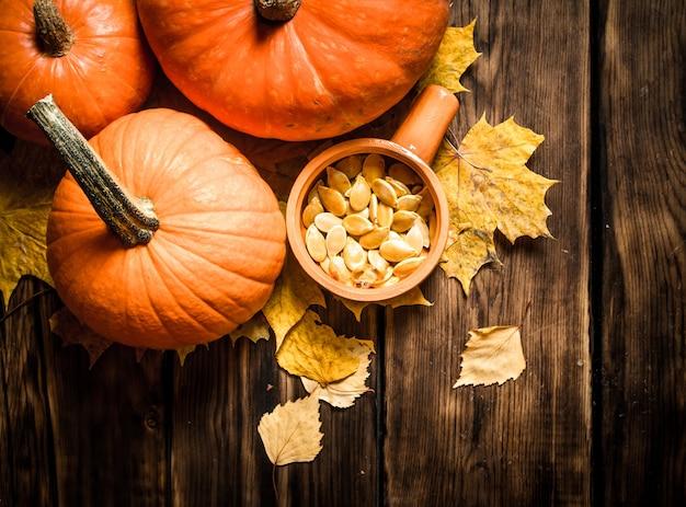 木製のテーブルにカエデの葉と秋の収穫カボチャの種