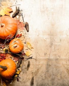 秋の収穫。葉のある熟したカボチャ。木製の背景に。