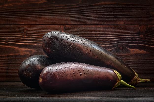 Autumn harvest, three eggplants on wooden desk surface