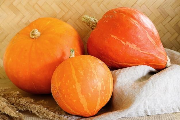 Осенний урожай. три спелых тыквы на деревенской поверхности