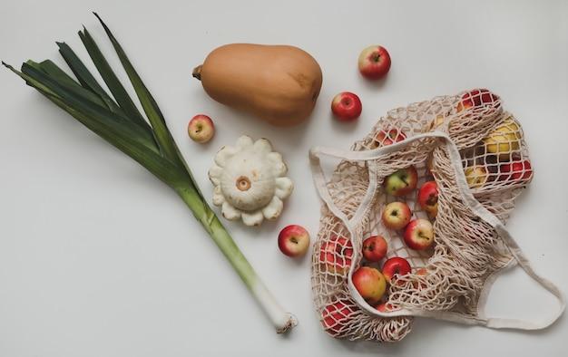 Осенний урожай с тыквенными яблоками и луком-пореем в сетчатой хозяйственной сумке на белом фоне