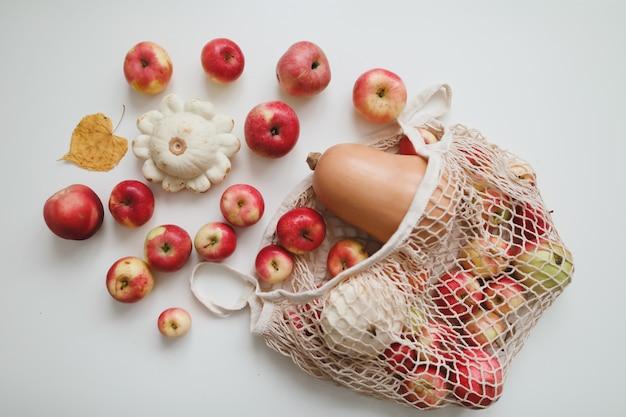Осенний урожай с тыквенными красными яблоками sqush в сетчатой эко-сумке на белом фоне