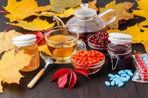 秋の健康飲料のコンセプト。秋の果実海クロウメモドキ、ガマズミ属の木、秋の葉とお茶のカップ。薬の代わりにビタミンを飲みます