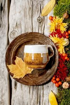 Сервировка стола осенних праздников. пустая керамическая тарелка и кружка ремесла на старом деревянном столе, украшенном осенними желтыми листьями, осенними ягодами, мхом и цветами. плоская планировка, копия пространства