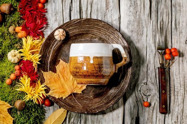 秋の休日テーブルの設定。空のクラフトセラミックプレートと秋の紅葉、秋の果実、苔、花で飾られた古い木製のテーブルのマグカップ。フラットレイアウト、コピースペース