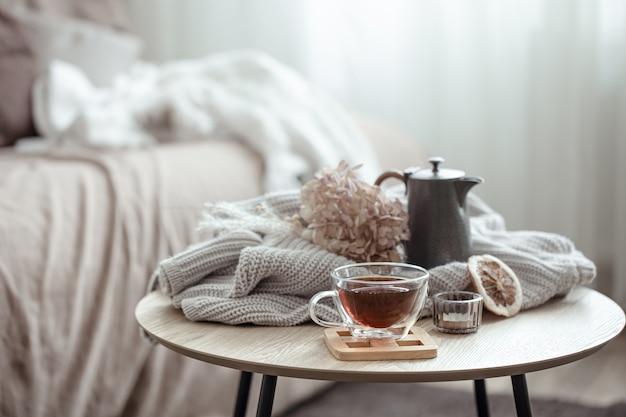 Осенняя домашняя композиция с чашкой чая, заварником и вязаным элементом.