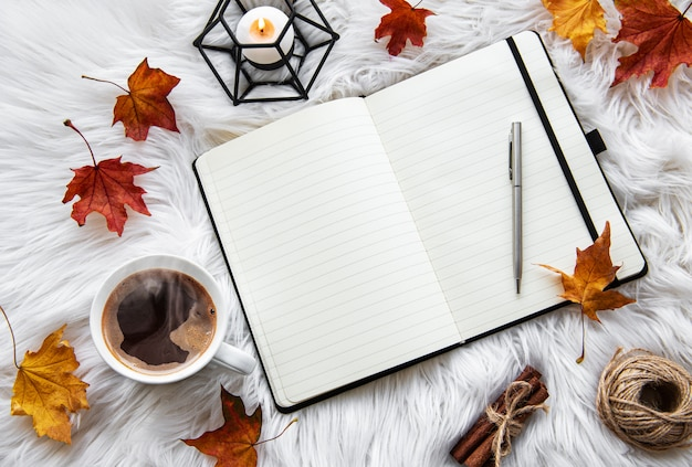 Autumn home cozy composition with coffee cup and notebook