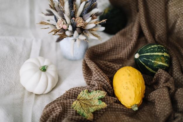 Осенний декор и композиция для дома с тыквами и листьями на пледе