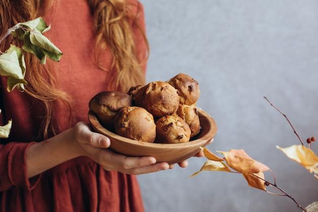 秋の自家製ケーキ-木製のボウルにフルーツを詰めたマフィン。