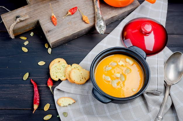 Autumn homemade pumpkin soup in clay bowl