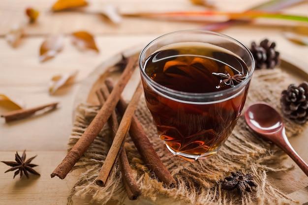 秋の熱いお茶のコンセプト。スパイスと落ち葉が木の上にあるガラスの熱いお茶。