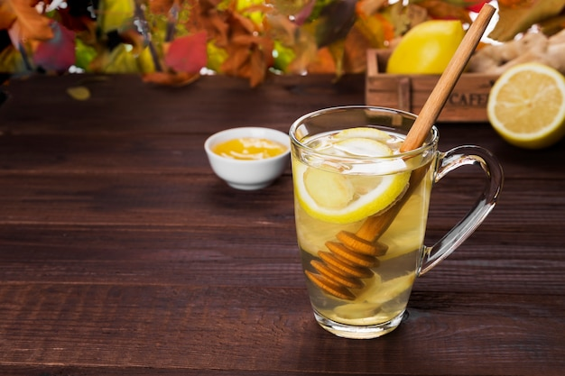 Autumn hot tea warming drink with ginger, honey and lemon in glas