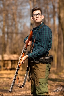 Autumn hunting season. man hunter with a gun. hunting in the woods