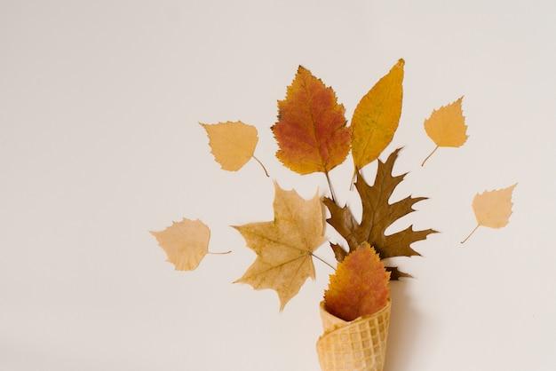 ベージュ色の背景にワッフルカップで落ちた黄色の葉と秋のアイスクリーム。秋のメニューコンセプト。フラットレイアウトおよびコピースペース