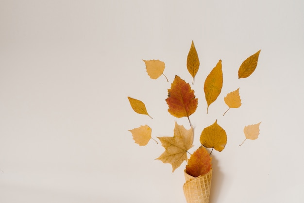Autumn ice cream with fallen yellow leaves in a waffle cup on a beige background. autumn menu concept.