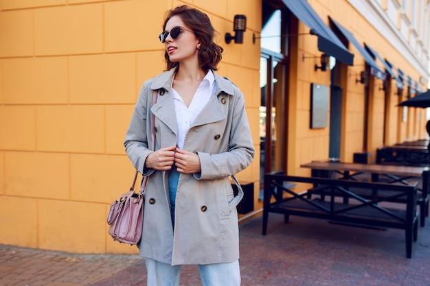 屋外を歩くベージュのコートを着たスタイリッシュな魅力的な女性の秋のイメージ。おしゃれなストリートルック。