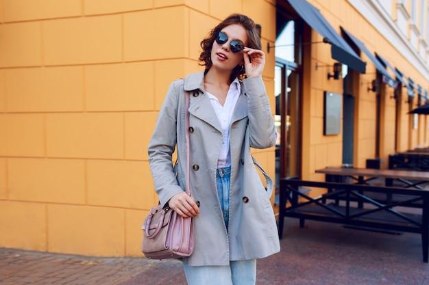 Изображение осени стильной очаровательной женщины в бежевом пальто гуляя напольное. модный уличный вид.