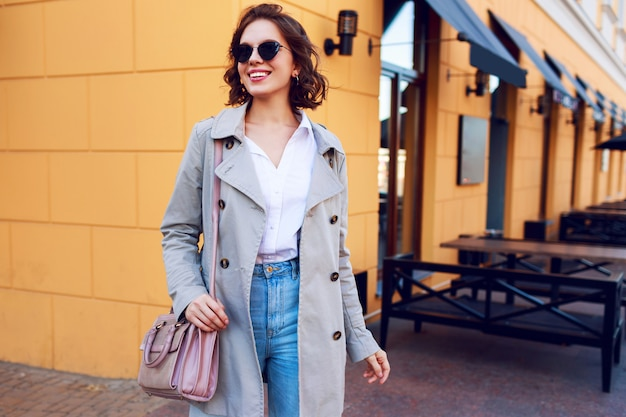 Autumn image of stylish charming female in beige coat walking outdoor. fashionable street look.