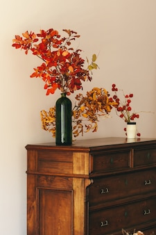 Autumn interior decoration with dry bouquet on wooden table