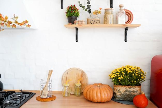 Autumn kitchen interior with shelfs, yellow flowers and pumpkin
