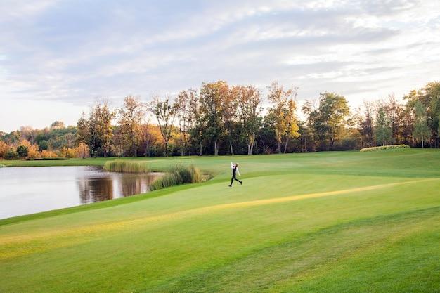 秋、湖、ゴルフコース。ゴルフコースの緑の芝生の上を走っている若い大人の女の子。女の子の自由。屋外