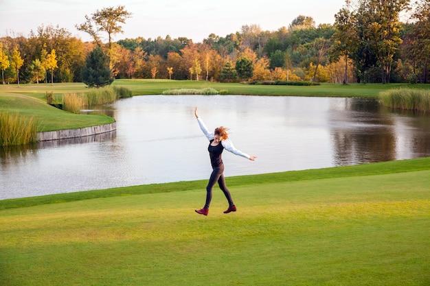 秋、湖、ゴルフコース。ゴルフコースの緑の芝生の上を走っている若い大人の女性。